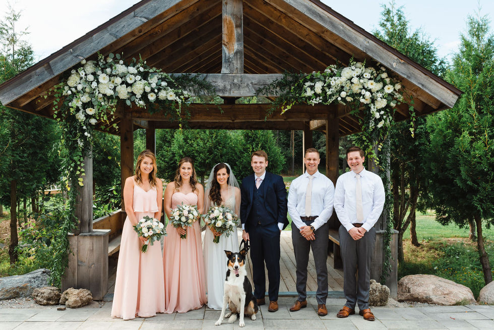 bride and groom standing in between their bridesmaids and groomsmen with their dog sitting in front of them during the special wedding at Carvers cottage in Toronto