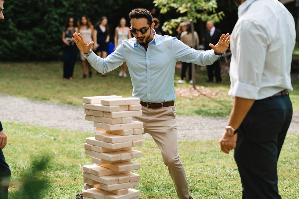 wedding guest jumping back with his hands up as he plays a giant version of jenga with another guest during special wedding at Carvers cottage in Pickering