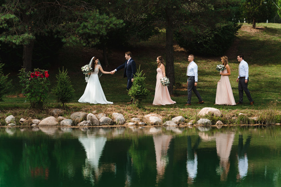 bride leading her groom and wedding party along a pond during their special wedding at Carvers cottage in Pickering
