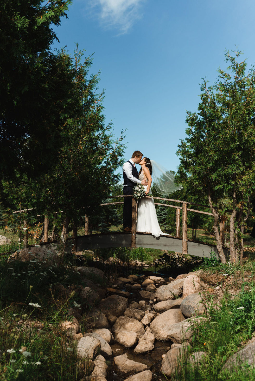 bride and groom kissing on a bridge over a stream during their special wedding at Carvers cottage in Pickering