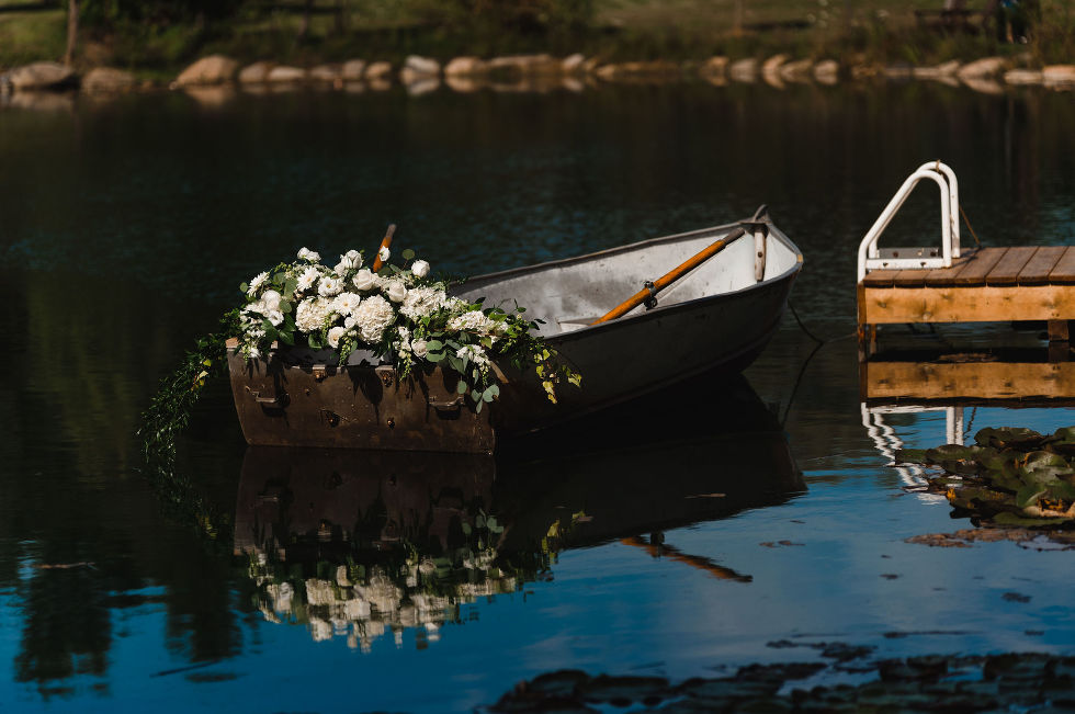 a row boat filled with white flowers sitting in a pond next to a dock at Carvers cottage how to make your wedding special