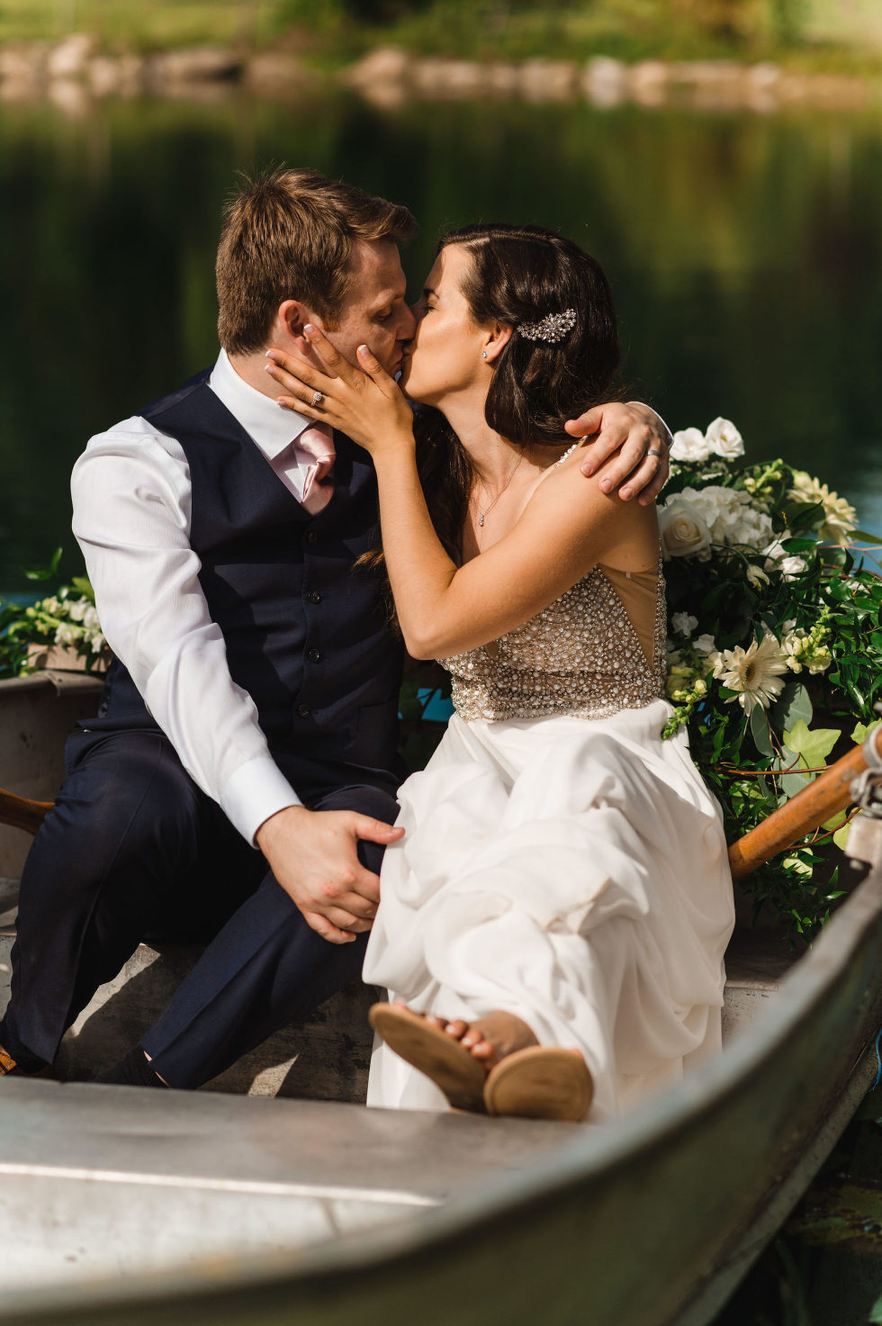bride and groom kissing while sitting in a row boat on a pond at Carvers cottage how to make your wedding special