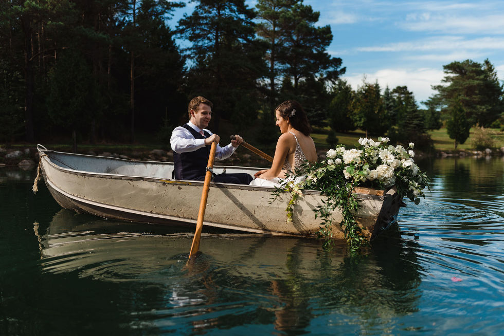 bride sitting next to a white floral bouquet in a row boat while her groom works the oars during the special wedding at Carvers cottage in Toronto
