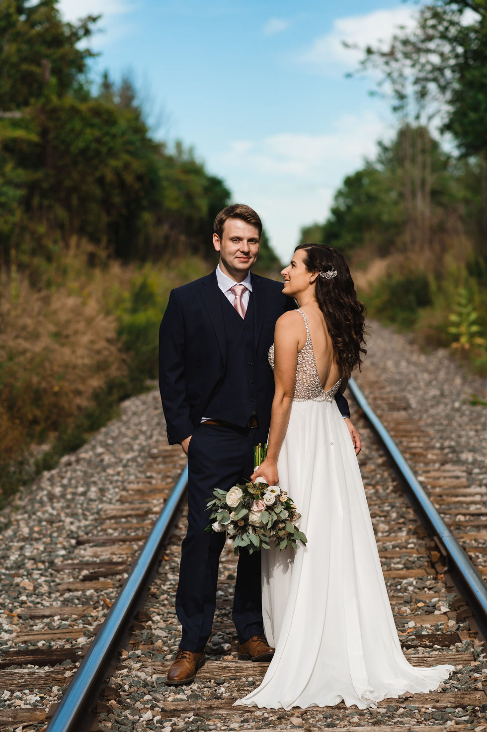 groom smiling as his bride looks at him adoringly while they stand over train tracks during wedding at Carvers cottage in Toronto