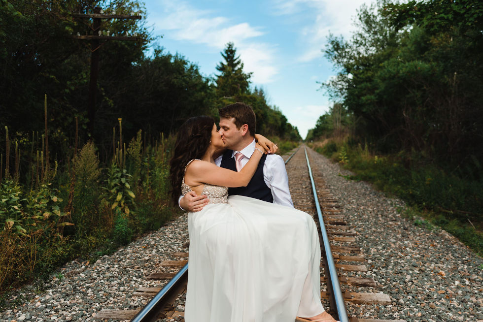 groom holding bride in his arms and kissing her while they stand over train tracks during wedding at Carvers cottage in Toronto