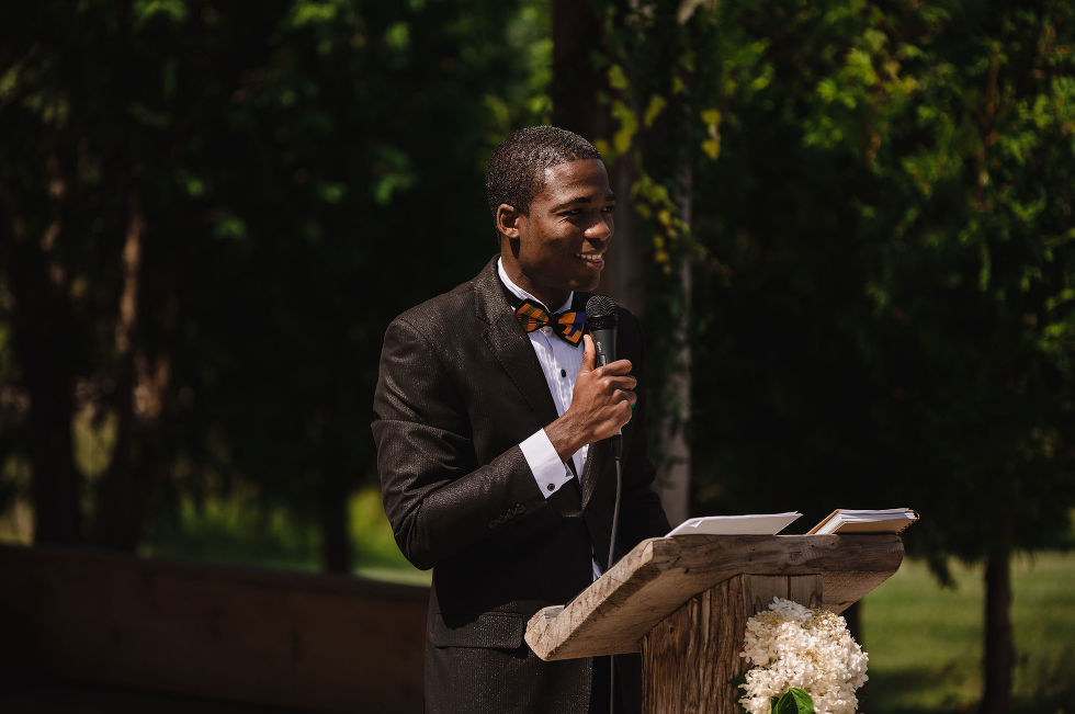 wedding officiant wearing black suit and orange bowtie speaking into a microphone at a wooden podium during ceremony at Carvers cottage in Pickering