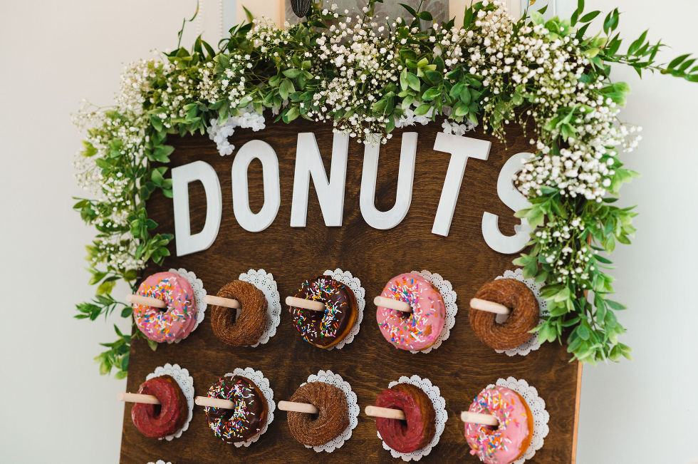 "a wooden board with white flowers on top and the word ""DONUTS"" written across it in white with donuts hanging below on pegs Carver cottage wedding Pickering"