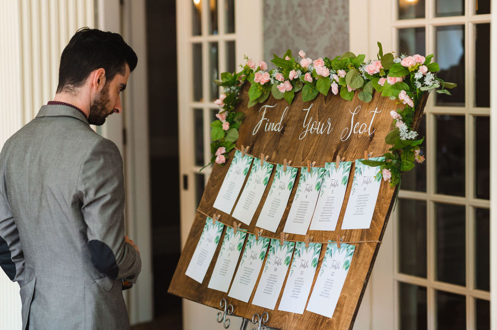 wedding guest looking at the seating plan board before wedding reception Toronto