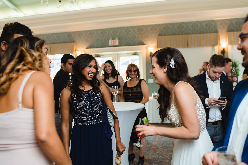 bride laughing with her guests inside the banquet hall at the Royal Ashburn in Toronto
