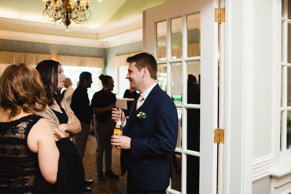 groom smiling and talking with his guests inside the banquet hall at the Royal Ashburn in Toronto