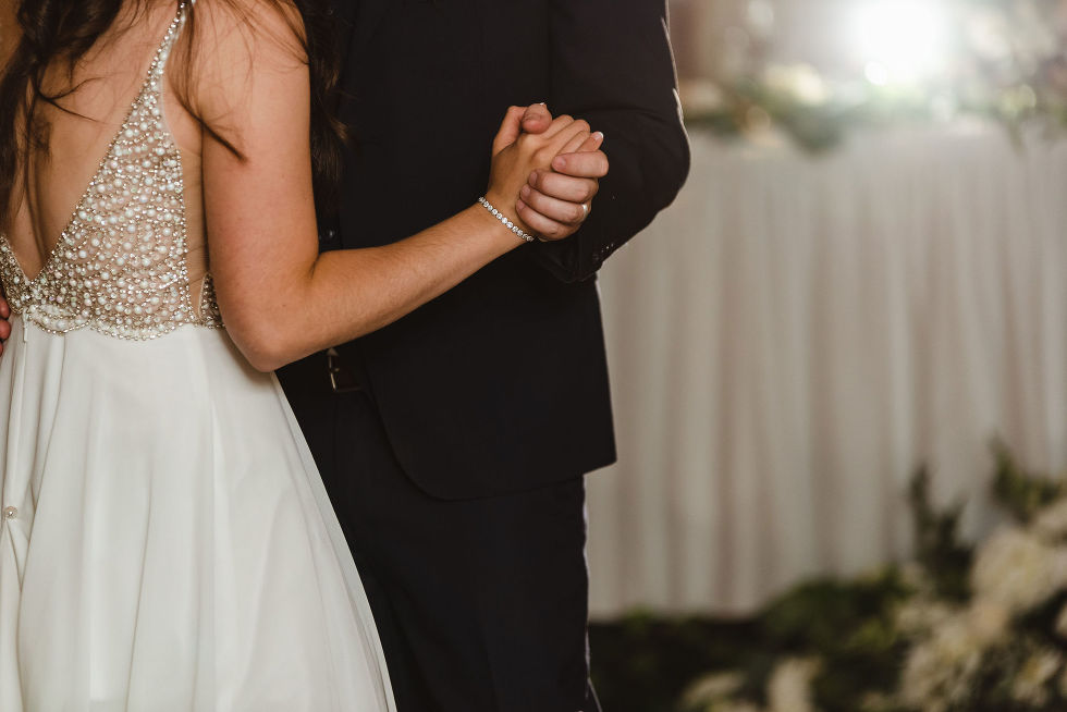 bride and groom holding hands as they dance during their special wedding reception at the Royal Ashburn in Toronto