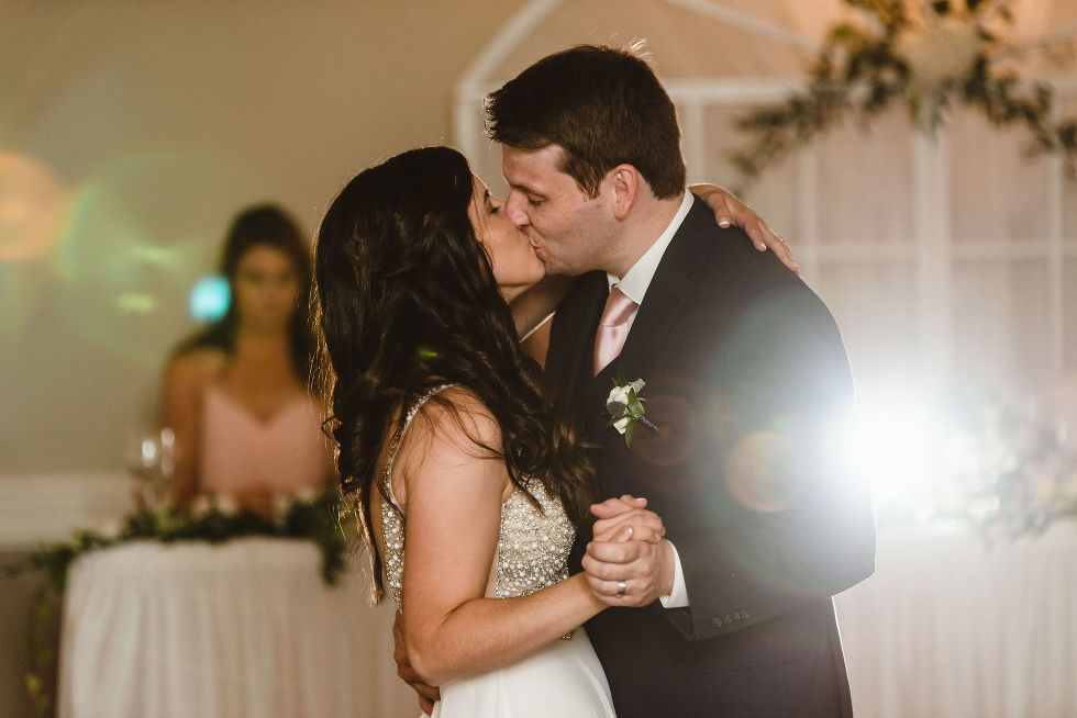 bride and groom holding hands and kissing as they dance during their special wedding reception at the Royal Ashburn in Toronto