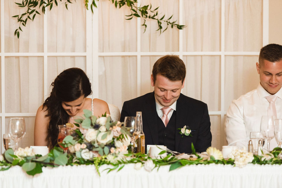 bride and groom bow their heads at their head table as grace is being said before their reception dinner during the special wedding at the Royal Ashburn in Toronto