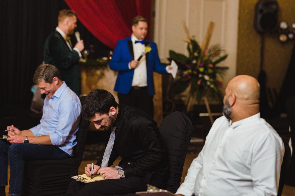 grooms reading game instructions into their microphones while seated guests are scribbling away on clipboards during a fun wedding at the Hilton Fallsview in Niagara Falls