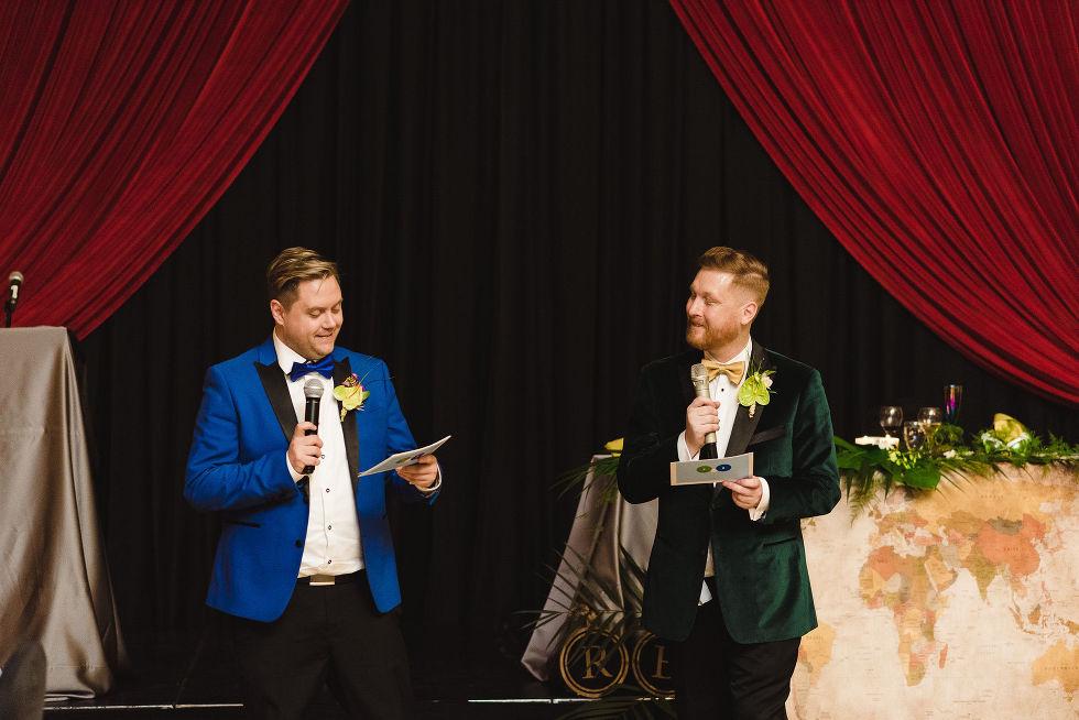 grooms reading their wedding speeches into their microphones during a fun wedding reception at the Hilton Fallsview in Niagara Falls