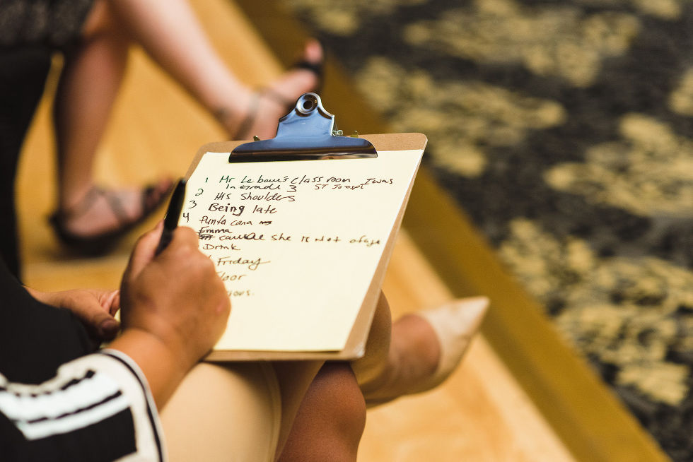 A wedding guest writing down her answers on a clipboard to a game being played during a fun wedding at the Hilton Fallsview in Niagara Falls