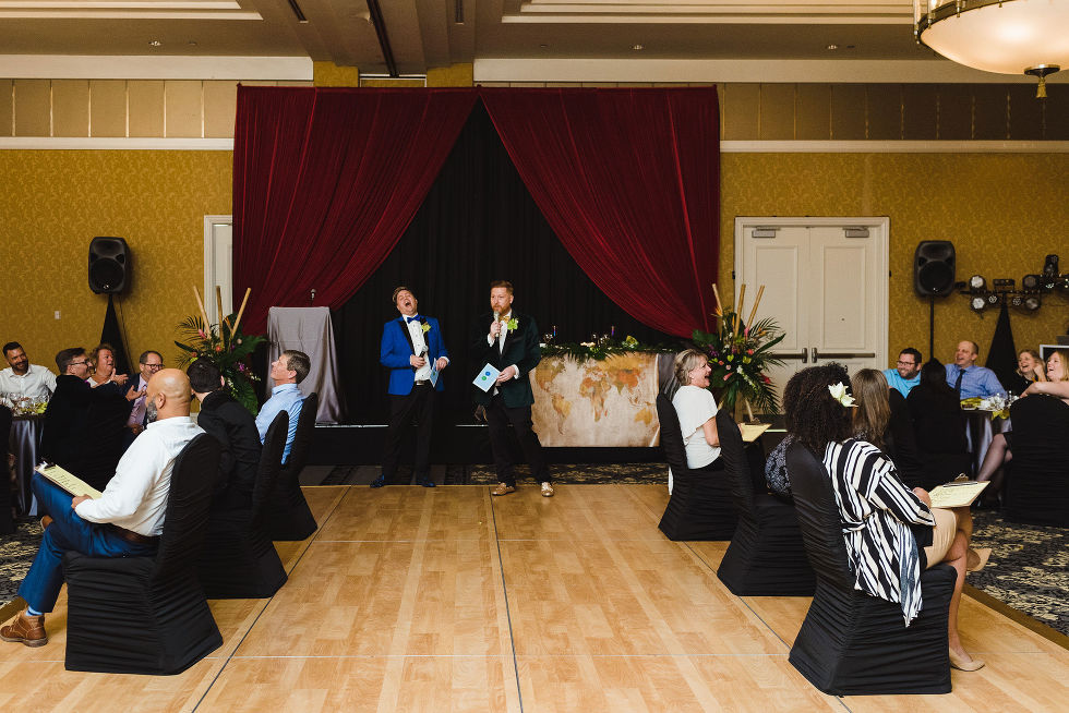 grooms laughing and reading out questions to their guests for their game during their fun wedding at the Hilton Fallsview in Niagara Falls