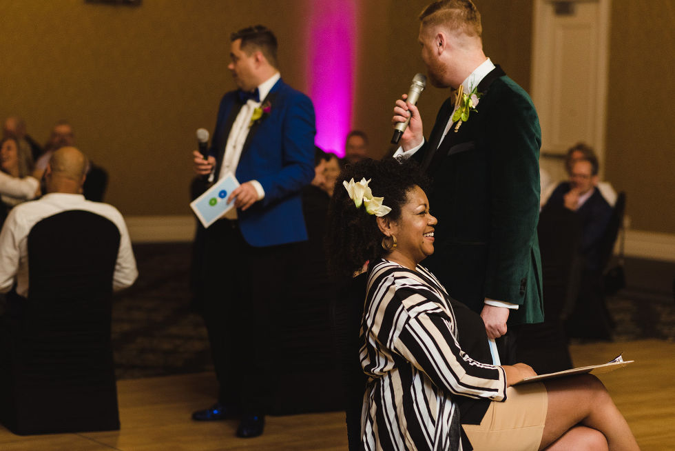 grooms instructing guests about the rules for the game they planned for their fun wedding at the Hilton Fallsview in Niagara Falls