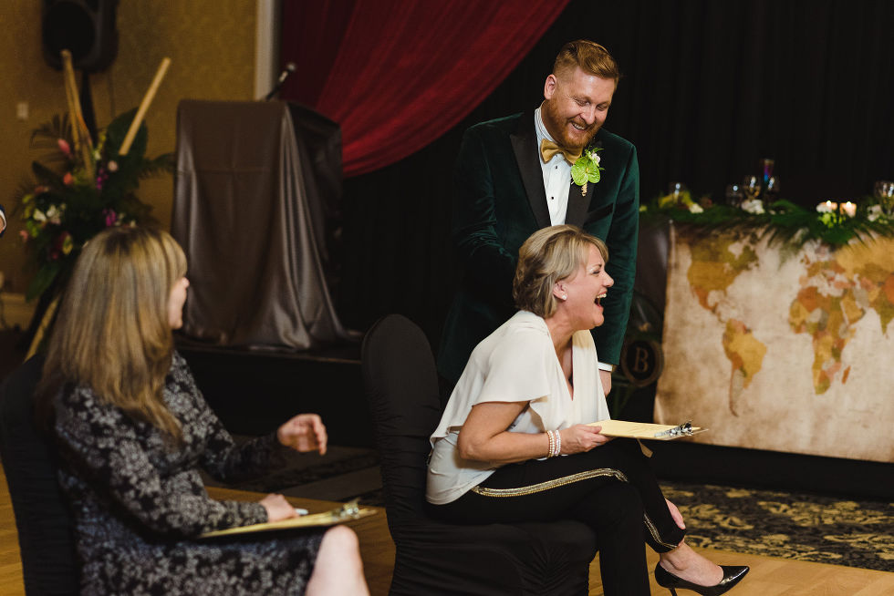 wedding guest and groom laughing during a fun wedding game for the reception at the Hilton Fallsview in Niagara Falls