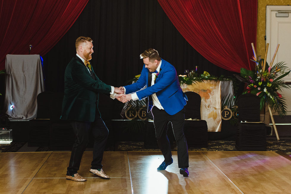 grooms holding hands and dancing during their fun wedding reception at the Hilton Fallsview in Niagara Falls