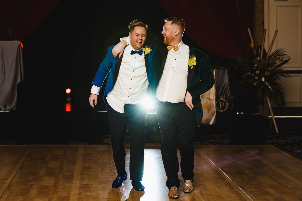 grooms with their arms around each other and laughing during their fun wedding at the Hilton Fallsview in Niagara Falls