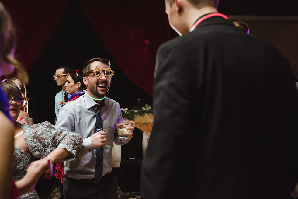 wedding guests wearing wacky glasses, while dancing and laughing during a fun wedding at the Hilton Fallsview in Niagara Falls