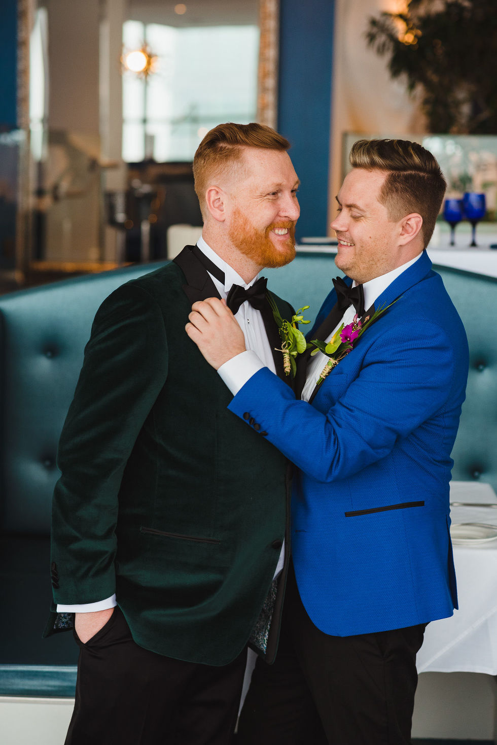 groom in bright blue suit brushing off the shoulder of his groom in a green suit before their wedding at the Hilton in Niagara Falls