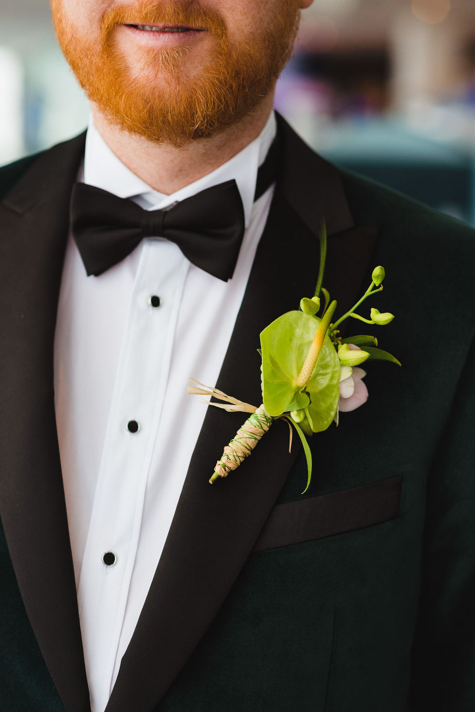groom in a green suit and dark bowtie with a green boutonniere on his lapel before his wedding at the Hilton hotel in Niagara Falls