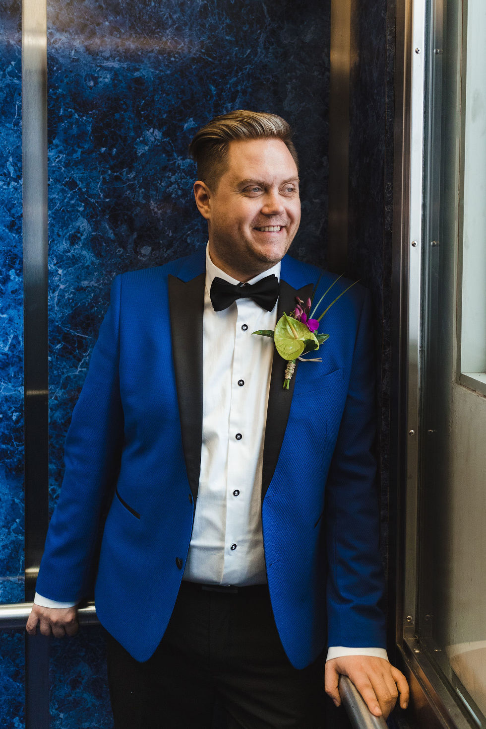 groom in a bright blue suit stands in front of a blue marble wall at the Hilton hotel in Niagara Falls before his wedding
