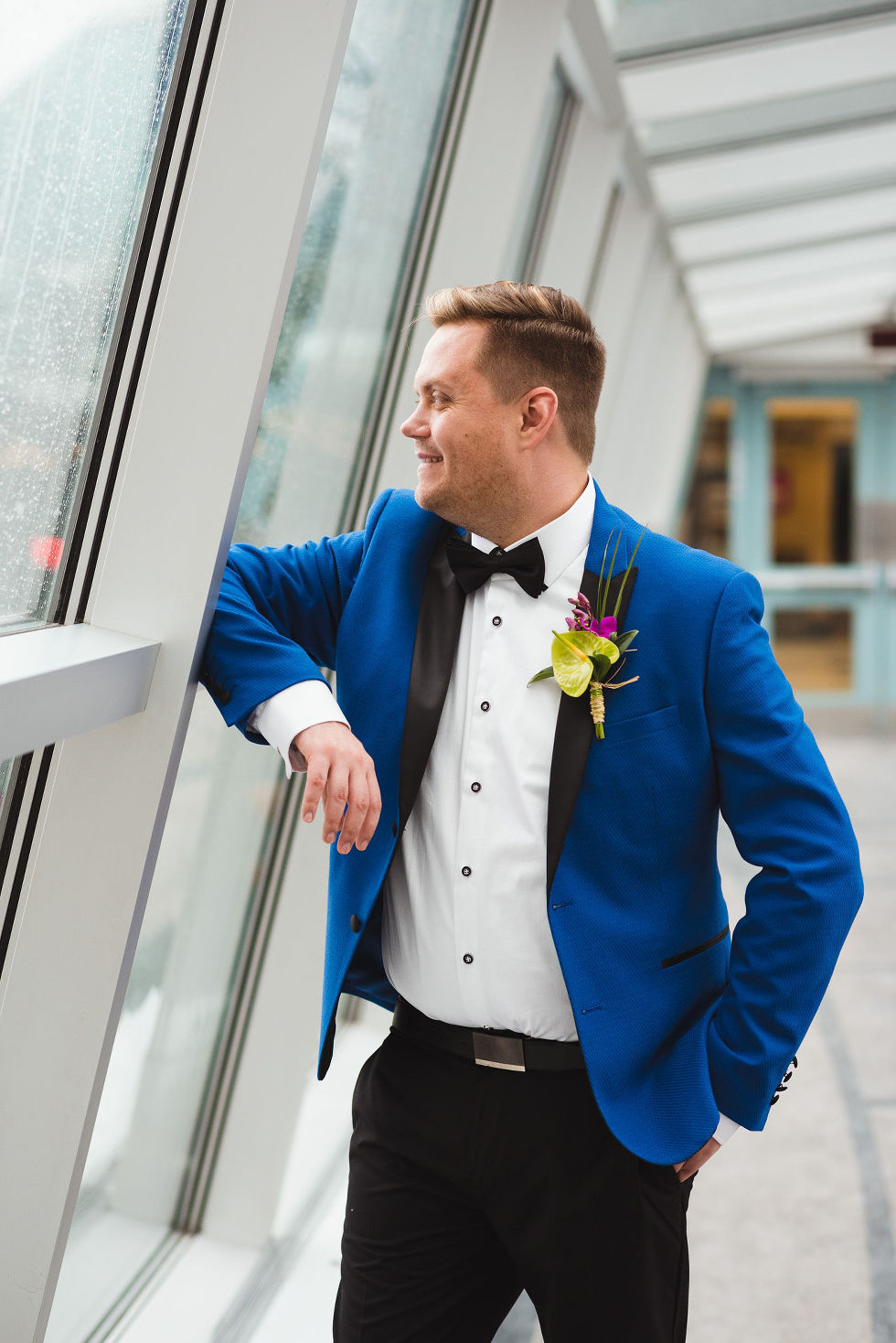 groom in bright blue suit stares out the window before his wedding ceremony at the Hilton Fallsview in Niagara Falls