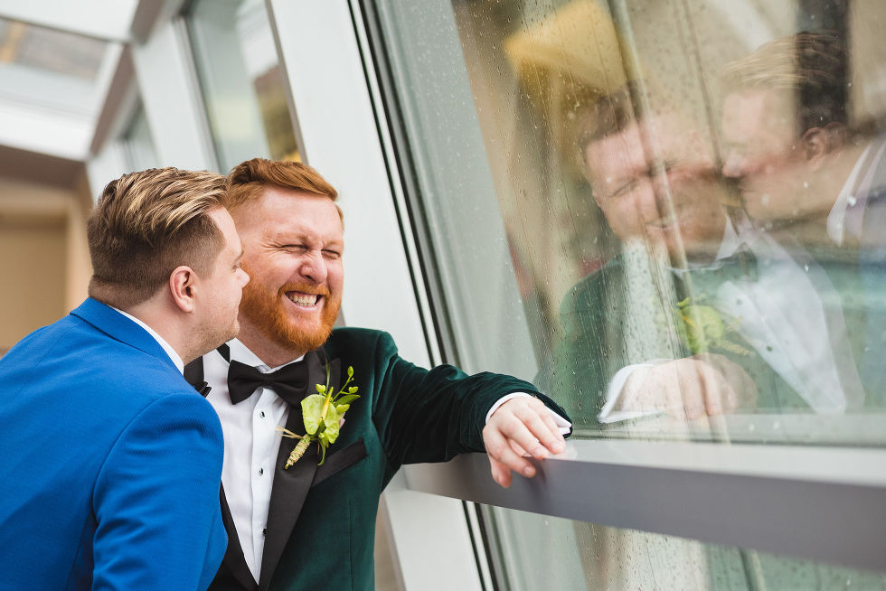 groom in bright blue suit leans into groom in green suit and makes him laugh before their wedding at the Hilton Fallsview in Niagara Falls