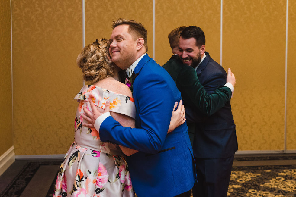grooms hugging their guests as they arrive in the golden banquet room at the Hilton Fallsview in Niagara Falls