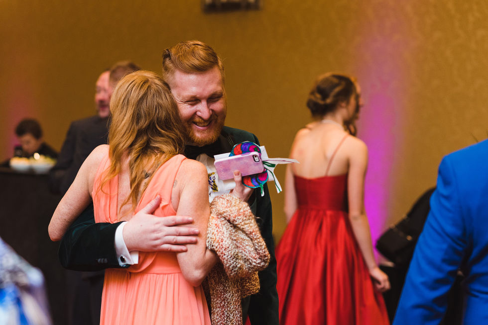 groom smiling as he hugs a wedding guest in a peach dress during his wedding at the Hilton Fallsview in Niagara Falls
