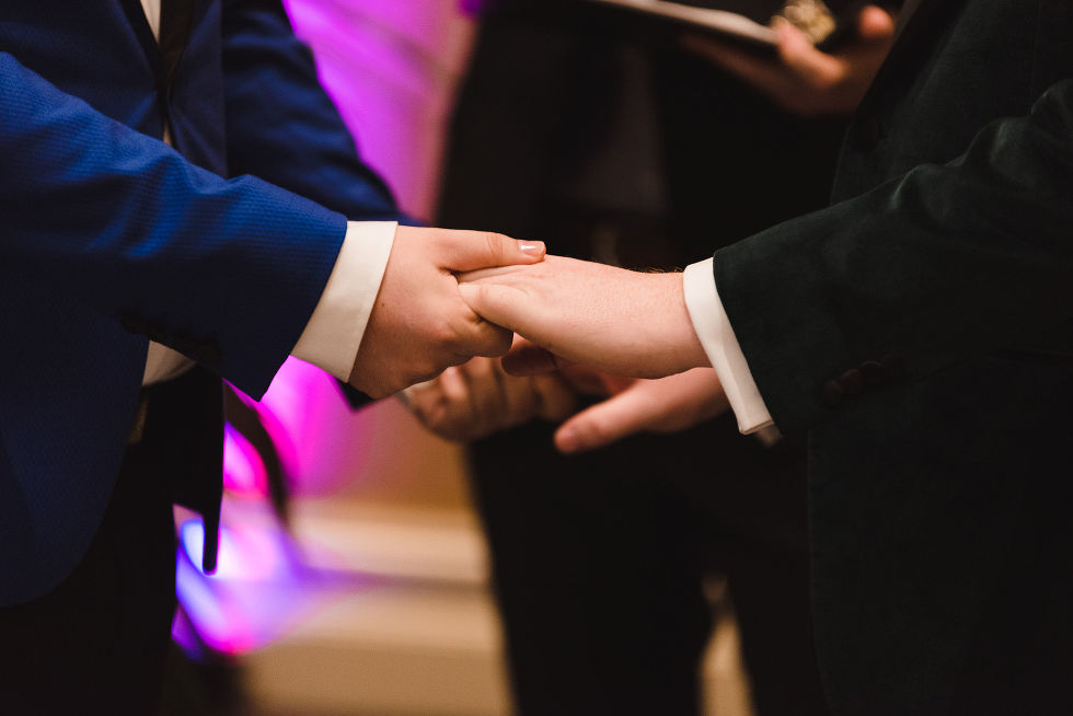 grooms holding hands during wedding ceremony at the Hilton Fallsview in Niagara Falls