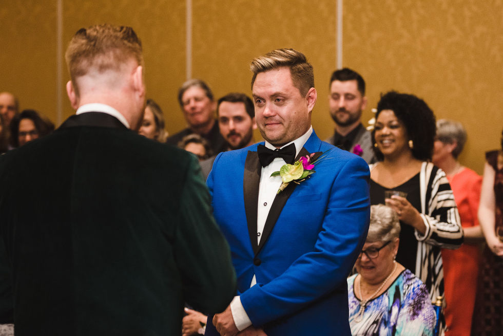 groom in bright blue suit getting teary eyed during wedding ceremony at the Hilton Fallsview in Niagara Falls