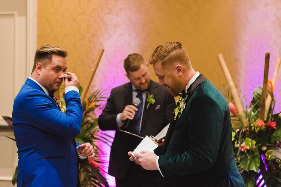 groom in bright blue suit wiping tears from his eyes while his groom reads vows during wedding ceremony at the Hilton Fallsview in Niagara Falls
