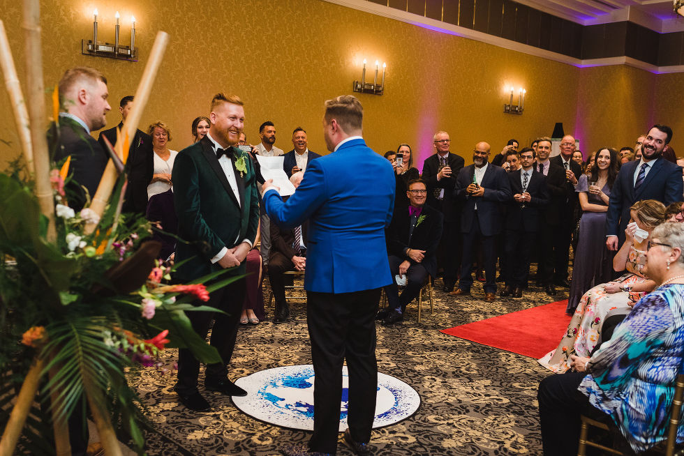 groom smiles and wedding guest look on as the other groom reads his vows aloud during wedding ceremony at the Hilton Fallsview in Niagara Falls