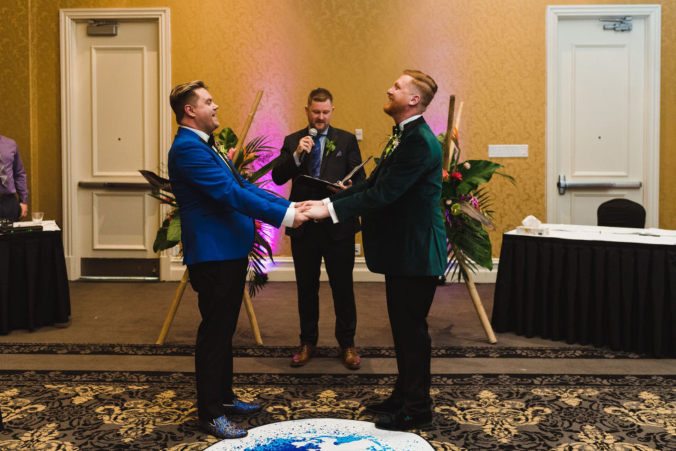grooms holding hands and laughing during wedding ceremony at the Hilton Fallsview in Niagara Falls