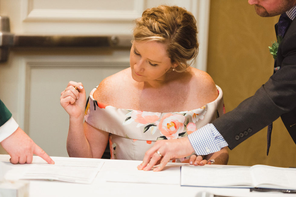 man pointing out where the witness signs the marriage certificate during wedding ceremony at the Hilton Fallsview in Niagara Falls