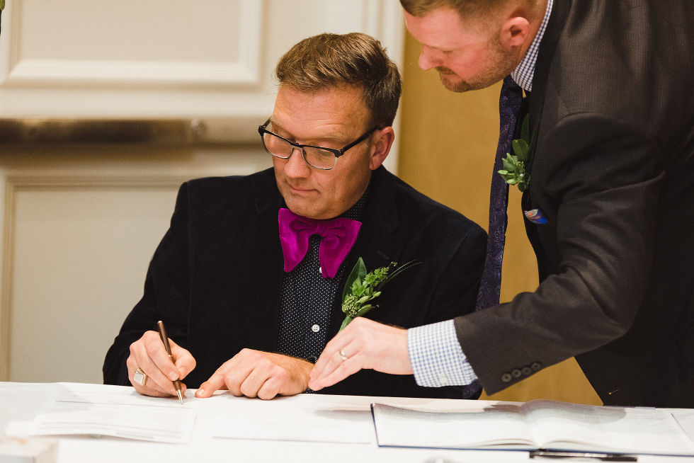 man pointing out where the witness signs the marriage certificate during ceremony at the Hilton Fallsview in Niagara Falls