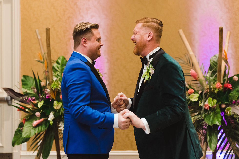 grooms holding hands and laughing hard after their wedding ceremony at the Hilton Fallsview in Niagara Falls