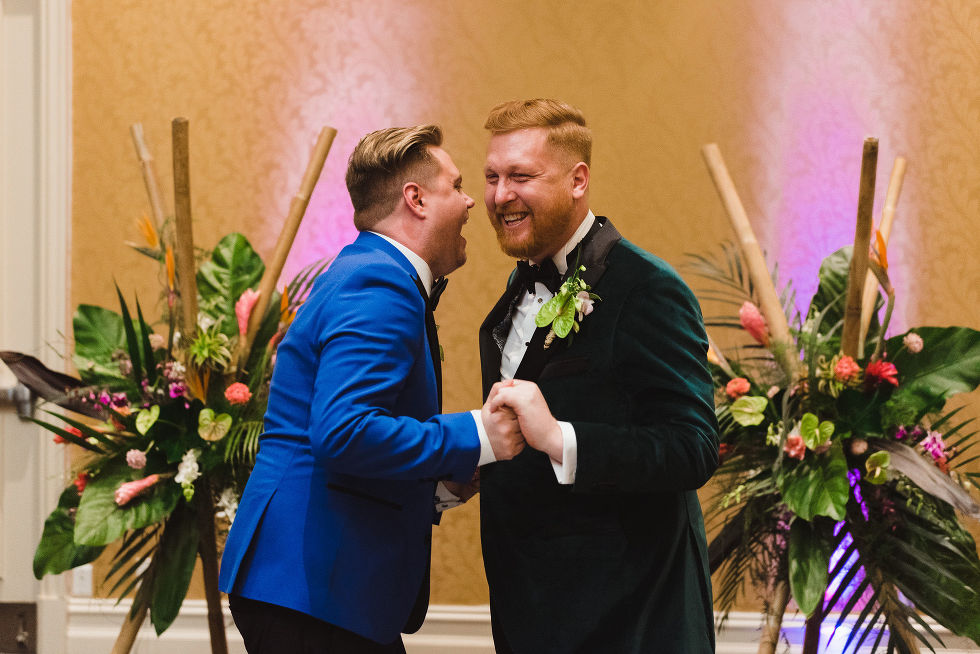 grooms holding hands and laughing hard after their wedding at the Hilton Fallsview in Niagara Falls