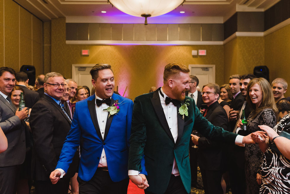 grooms holding hands walking past their guests as they exit their wedding ceremony at the Hilton Fallsview in Niagara Falls