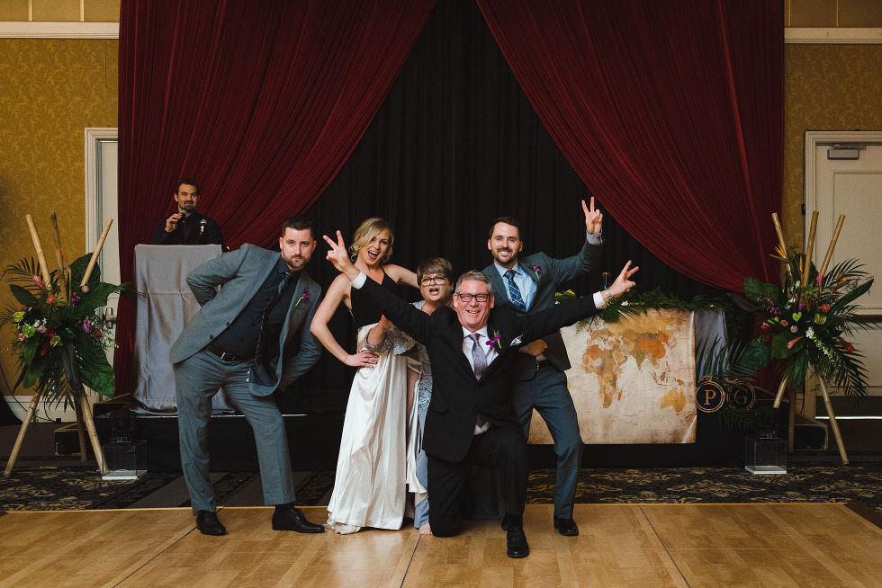 wedding guests posing together on the dance floor and holding up peace signs with their hands during wedding reception at the Hilton Fallsview in Niagara Falls