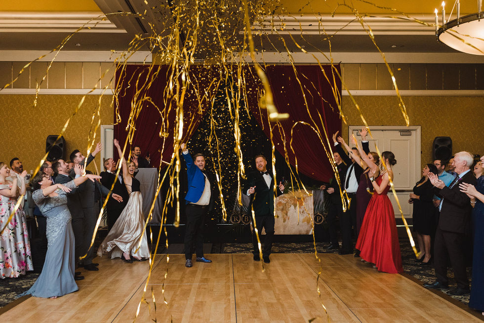 gold streamers shoot from a canon during the wedding reception at the Hilton Fallsview in Niagara Falls