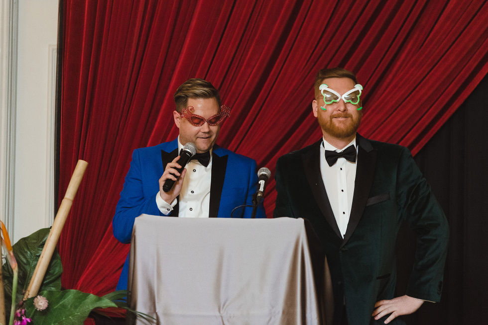 grooms wearing wacky glasses as they read speeches at the podium during their wedding reception at the Hilton Fallsview in Niagara Falls