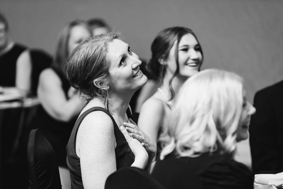 wedding guest with her hands over her chest and smiling during wedding speeches at the Hilton Fallsview in Niagara Falls