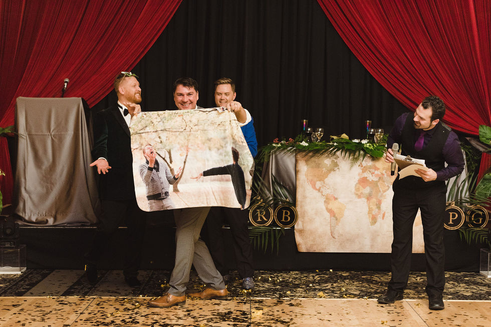 wedding guest holding up large picture of the grooms during the fun wedding reception at the Hilton Fallsview in Niagara Falls