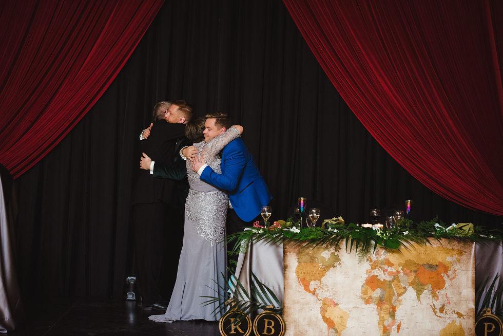 grooms hugging parents during fun wedding reception at the Hilton Fallsview in Niagara Falls