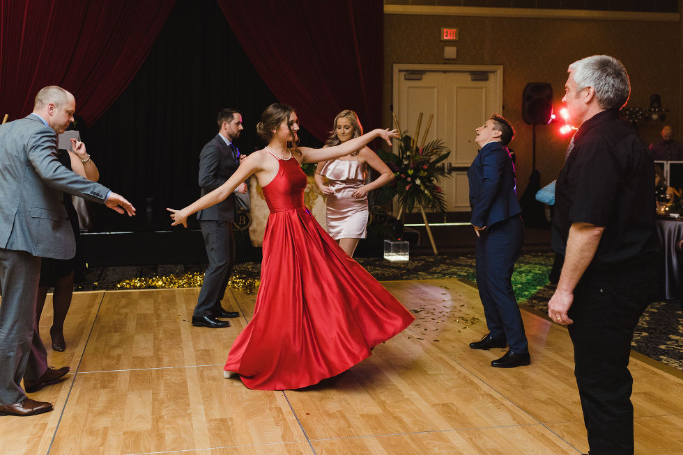 wedding guests dancing and a girl in a red dress twirling during a fun wedding reception at the Hilton Fallsview in Niagara Falls